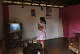 A Sri Lankan Christian catholic woman prays inside her home watching live transmission of Sri Lankan Archbishop Cardinal Malcolm Ranjith, in Negombo, Sri Lanka, Sunday, April 28, 2019. Sri Lanka's Catholics celebrated Sunday Mass in their homes by a televised broadcast as churches across the island nation shut over fears of militant attacks, a week after the Islamic State-claimed Easter suicide bombings killed over 250 people. (AP Photo/Manish Swarup)