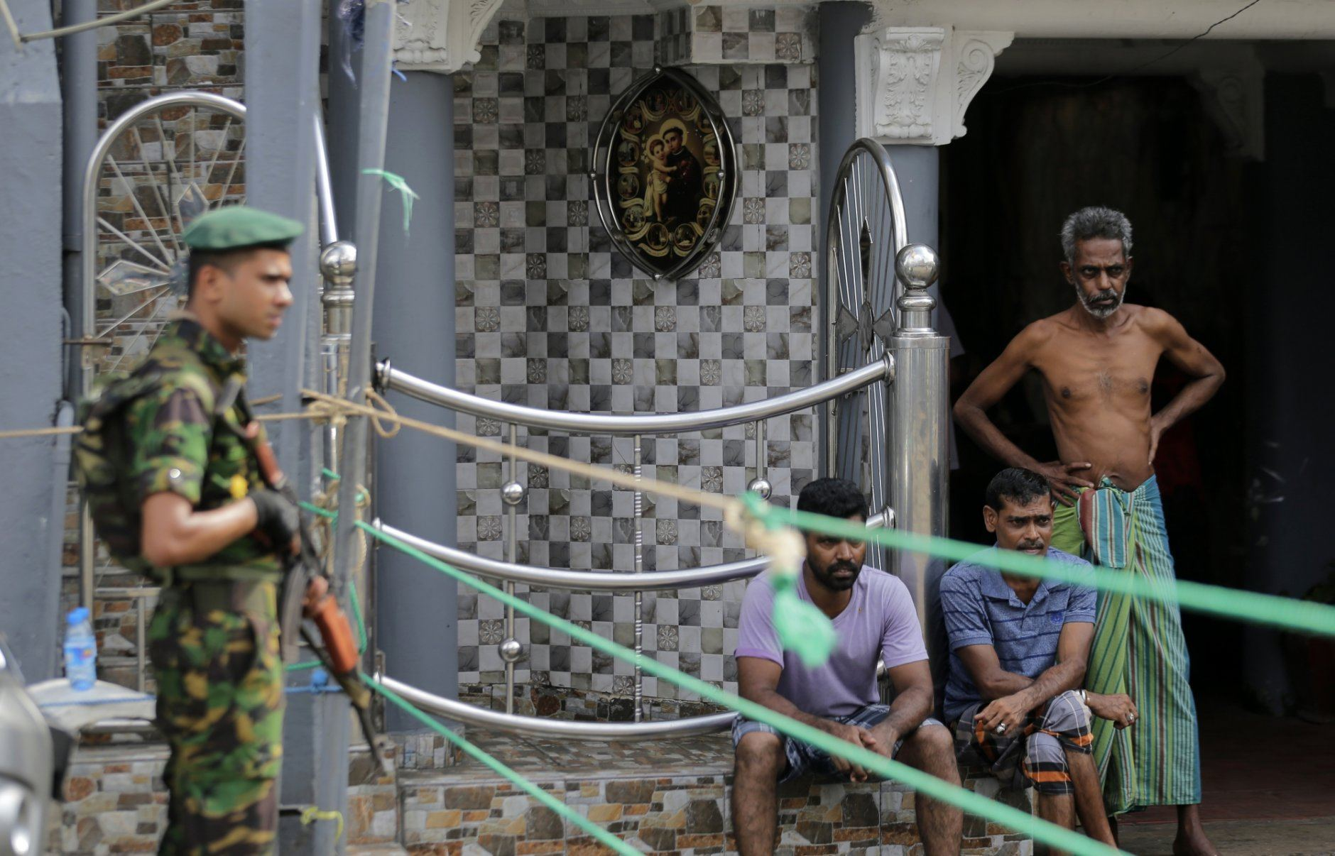 A Sri Lankan police commando secure the area of the exploded St. Anthony's Church on Easter Sunday attacks as people wait next to a small roadside in Colombo, Sri Lanka, Sunday, April 28, 2019. Sri Lanka's Catholics on Sunday awoke preparing to celebrate Mass in their homes by a televised broadcast as churches across the island shut over fears of militant attacks, a week after the Islamic State-claimed Easter suicide bombings. (AP Photo/Eranga Jayawardena)