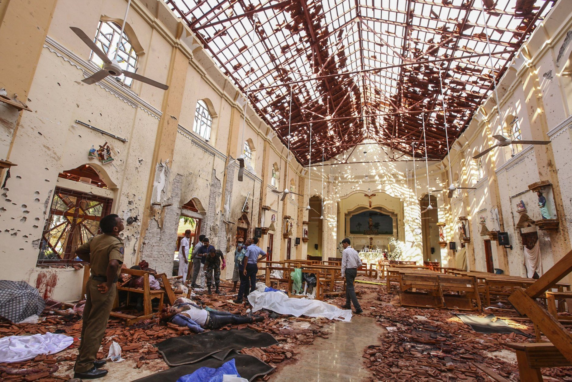 Dead bodies of victims lie inside St. Sebastian's Church damaged in blast in Negombo, north of Colombo, Sri Lanka, Sunday, April 21, 2019.  More than hundred were killed and hundreds more hospitalized with injuries from eight blasts that rocked churches and hotels in and just outside of Sri Lanka's capital on Easter Sunday, officials said, the worst violence to hit the South Asian country since its civil war ended a decade ago. (AP Photo/Chamila Karunarathne)