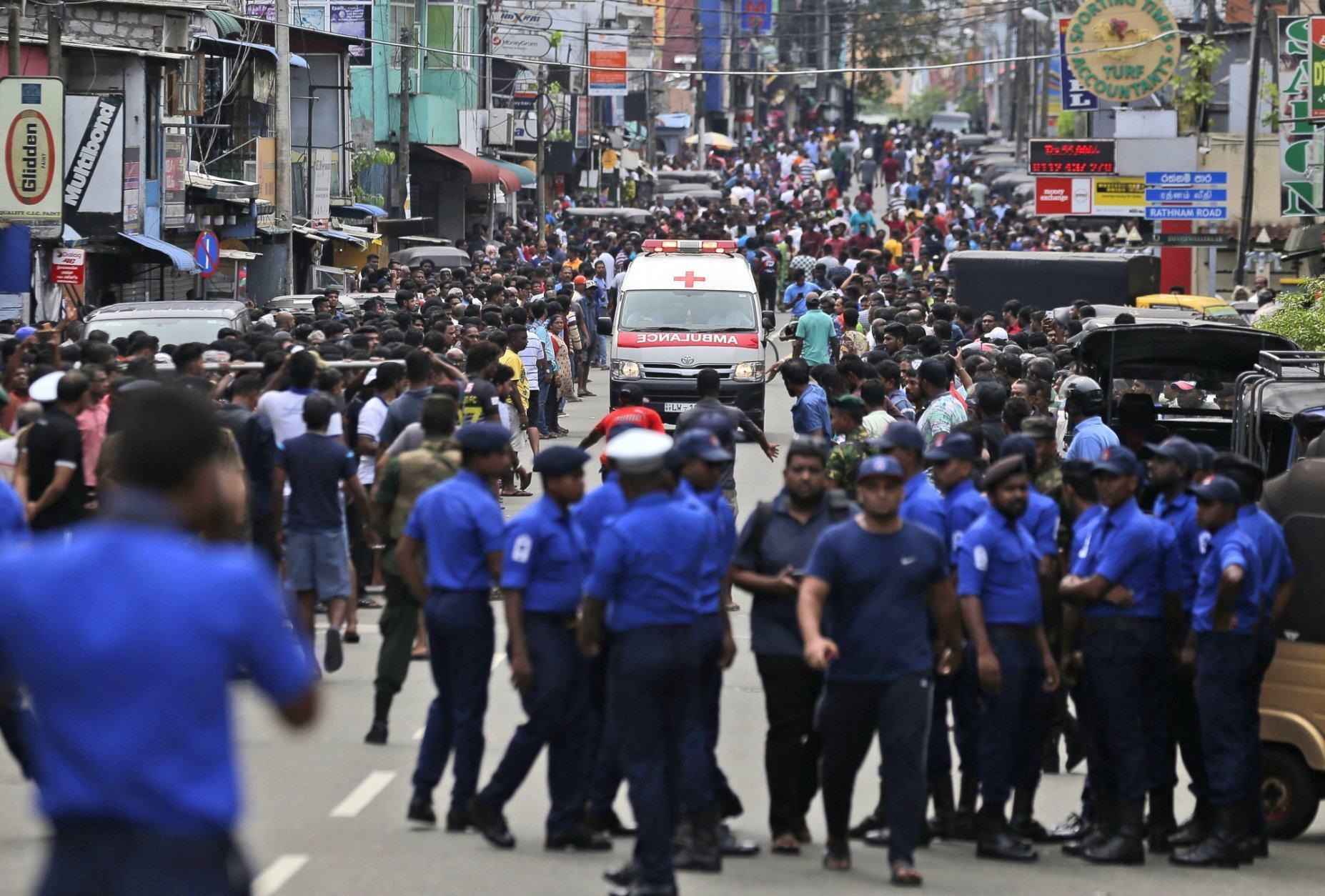 Sri Lankan police officers clear the road as an ambulance drives through carrying injured of Church blasts in Colombo, Sri Lanka, Sunday, April 21, 2019. A Sri Lanka hospital spokesman says several blasts on Easter Sunday have killed dozens of people. (AP Photo/Eranga Jayawardena)