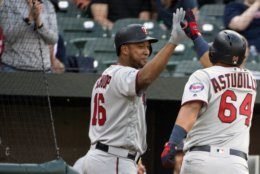 Minnesota Twins' Willians Astudillo (64) celebrates with Jonathan Schoop (16) in the second inning of a baseball game against the Baltimore Orioles, Saturday, April 20, 2019, in Baltimore. (AP Photo/Tommy Gilligan)