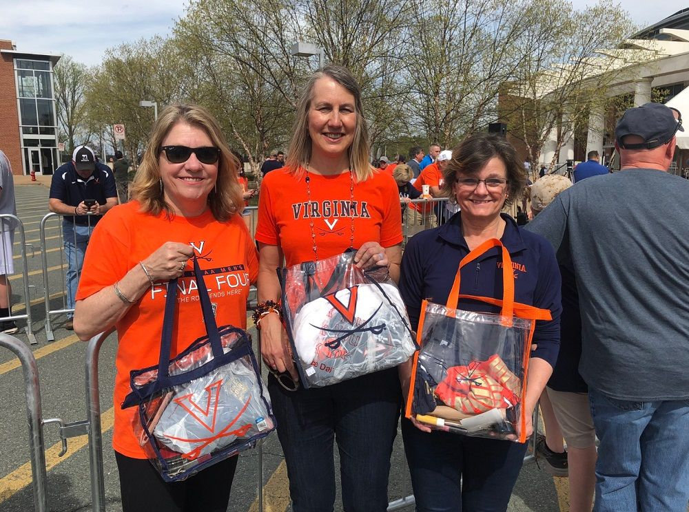 """Rocking the clear bag needed to go into John Paul Jones Arena are Lori O'Toole of Richmond, Virginia, and Jeanne Landis and Vickie Sandifer of Lynchburg, Virginia. UVA's win: """"is something be proud of."""" (WTOP/Kristi King)"""
