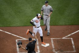 Baltimore Orioles third baseman Renato Nunez, middle, scores on a wild pitch by New York Yankees starting pitcher James Paxton, top, during the first inning of a baseball game, Thursday, April 4, 2019, in Baltimore. (AP Photo/Nick Wass)