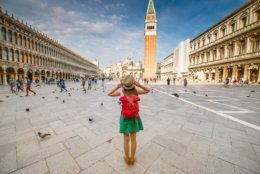 Young female traveler with hat and backpack standing on San Marco square with tower and basilica on the background in Venice. Back view with copy space