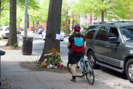 A cyclist stops at the crash scene where D.C. cycling advocate Dave Salovesh was killed on Friday. (WTOP/Kate Ryan)