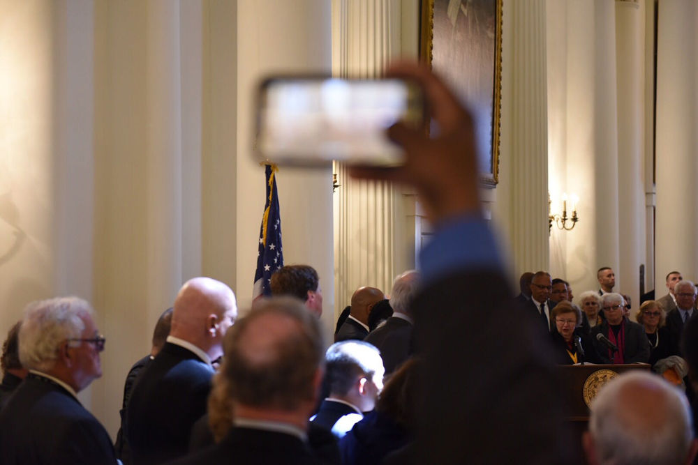 A member of the crowd reaches up to get a photo of the casket of the late House Speaker, Michael Busch. Hundreds gathered to file past and pay their respects to Speaker Busch's wife and daughters. (WTOP/Kate Ryan)