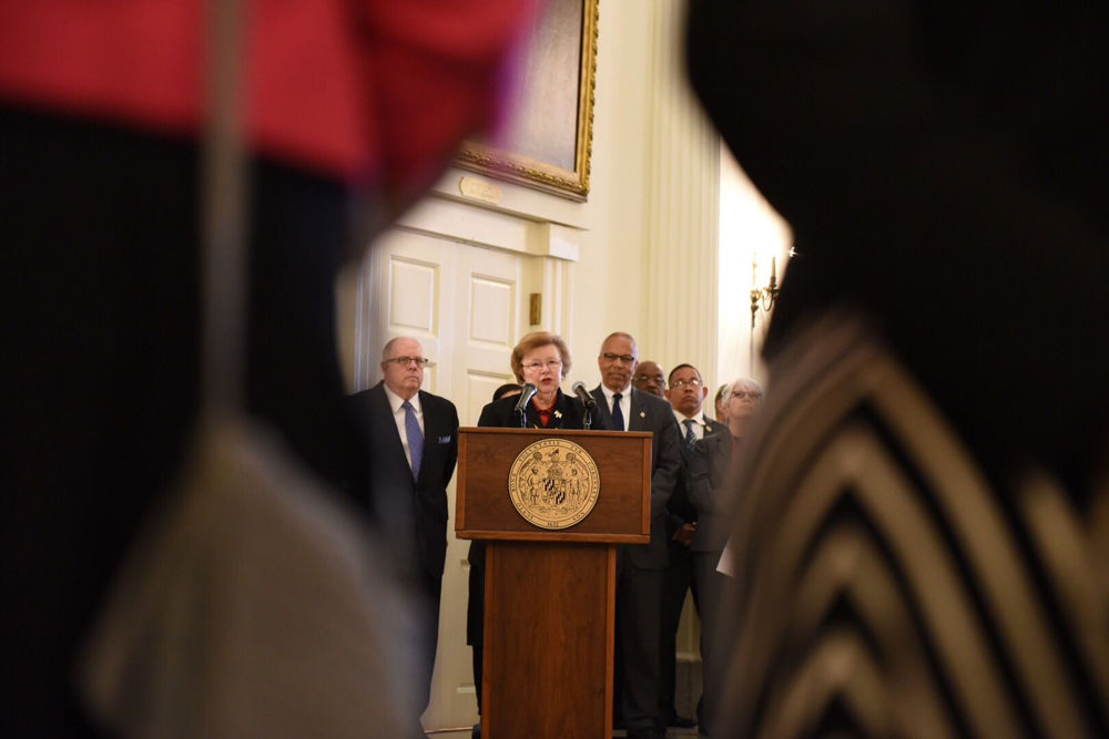 Sen. Barbara Mikulski speaks at the ceremony where the late House Speaker Michael Busch lies in state. She is flanked by Gov. Larry Hogan and Lt. Gov. Boyd Rutherford. (WTOP/Kate Ryan)