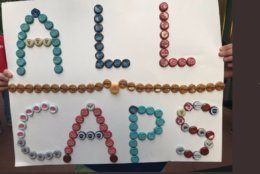 Fann shows All Caps signs made of bottle caps during Game 7, on Wednesday, April 24, 2019. (WTOP/Michelle Basch)