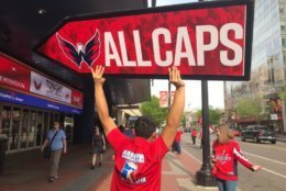 A sign spinner holds an All Caps sign during Game 7. (WTOP/Michelle Basch)
