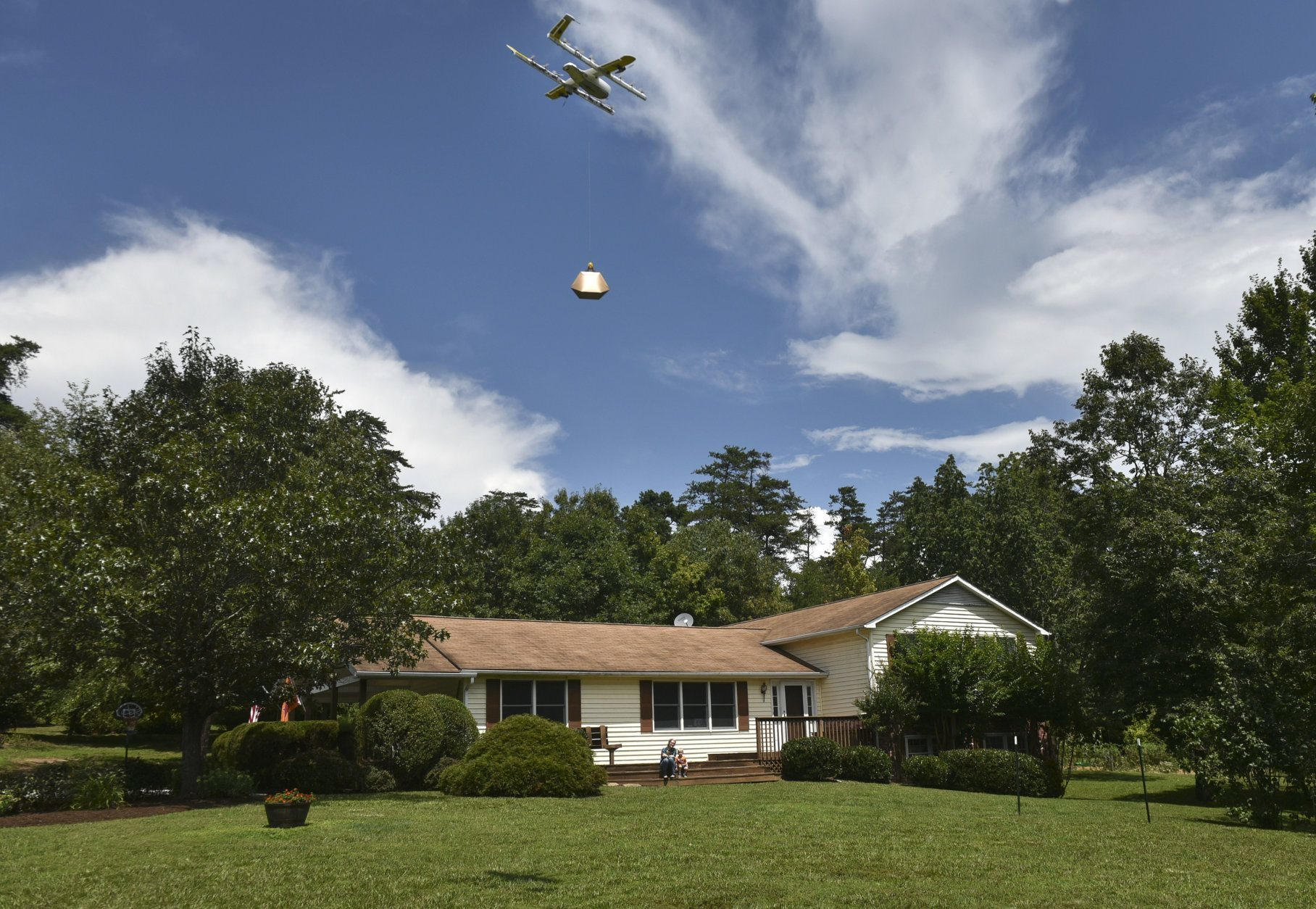 In this Tuesday, Aug, 7, 2018, photo a Wing Hummingbird drone from Project Wing arrives and sets down its package at the delivery location in Blacksburg, Va. Wing, a subsidiary of Google's parent corporation Alphabet, hasn't been allowed to fly long distances, over people and beyond the pilot's line of sight. That changed when Virginia was selected as one of 10 areas to participate in an experimental program that would lower barriers on the technology. (Michael Shroyer via AP)
