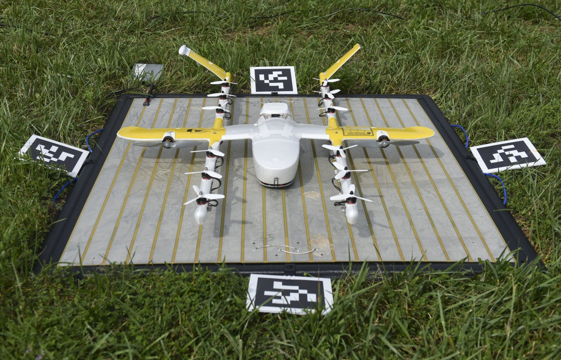 In this Tuesday, Aug, 7, 2018, photo a Wing Hummingbird drone from Project Wing sits on its launch pad and awaits flight at Kentland Farms in Blacksburg, Va. Wing, a subsidiary of Google's parent corporation Alphabet, hasn't been allowed to fly long distances, over people and beyond the pilot's line of sight. That changed when Virginia was selected as one of 10 areas to participate in an experimental program that would lower barriers on the technology. (Michael Shroyer via AP)
