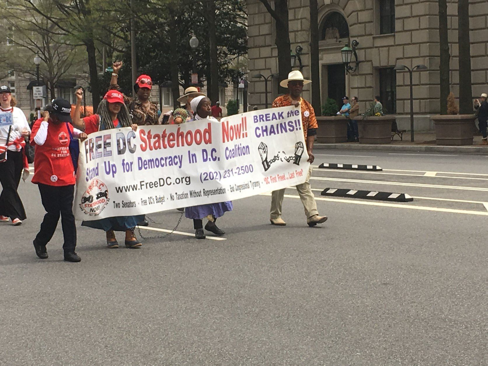 Parade participants hold a banner for statehood during D.C.'s Emancipation Day Parade on Saturday, April 13, 2019. (WTOP/Rick Massimo)