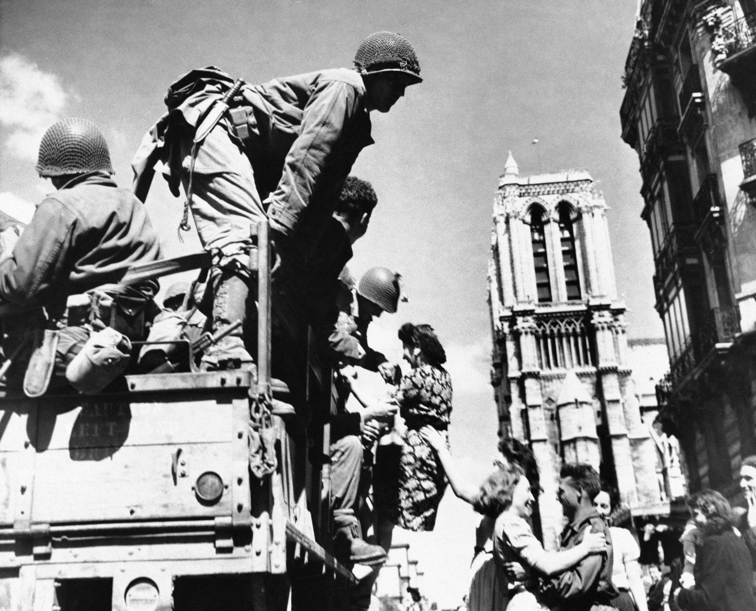 United States soldiers are shown being joyfully greeted by French women in the shadow of Notre Dame Cathedral in Paris, August 28, 1944. They dance and one girl seems to be pulling a soldier from the truck. (AP Photo)
