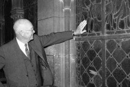 President Dwight Eisenhower runs his hand over surface of one of the stained glass windows in Cathedral of Notre Dame, May 18, 1960 as he toured churches din the French Capital. (AP Photo)