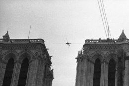 Philippe Petit, a 21-year-old professional tightrope walker, appears as the tiny figure as he lies on a tightrope, strung 225 feet above the ground, between the two towers of Notre Dame Cathedral, Paris, France on June 26, 1971, during a stunt which lasted several hours, with police unable to bring him down. (AP Photo/Str/Cardenas)