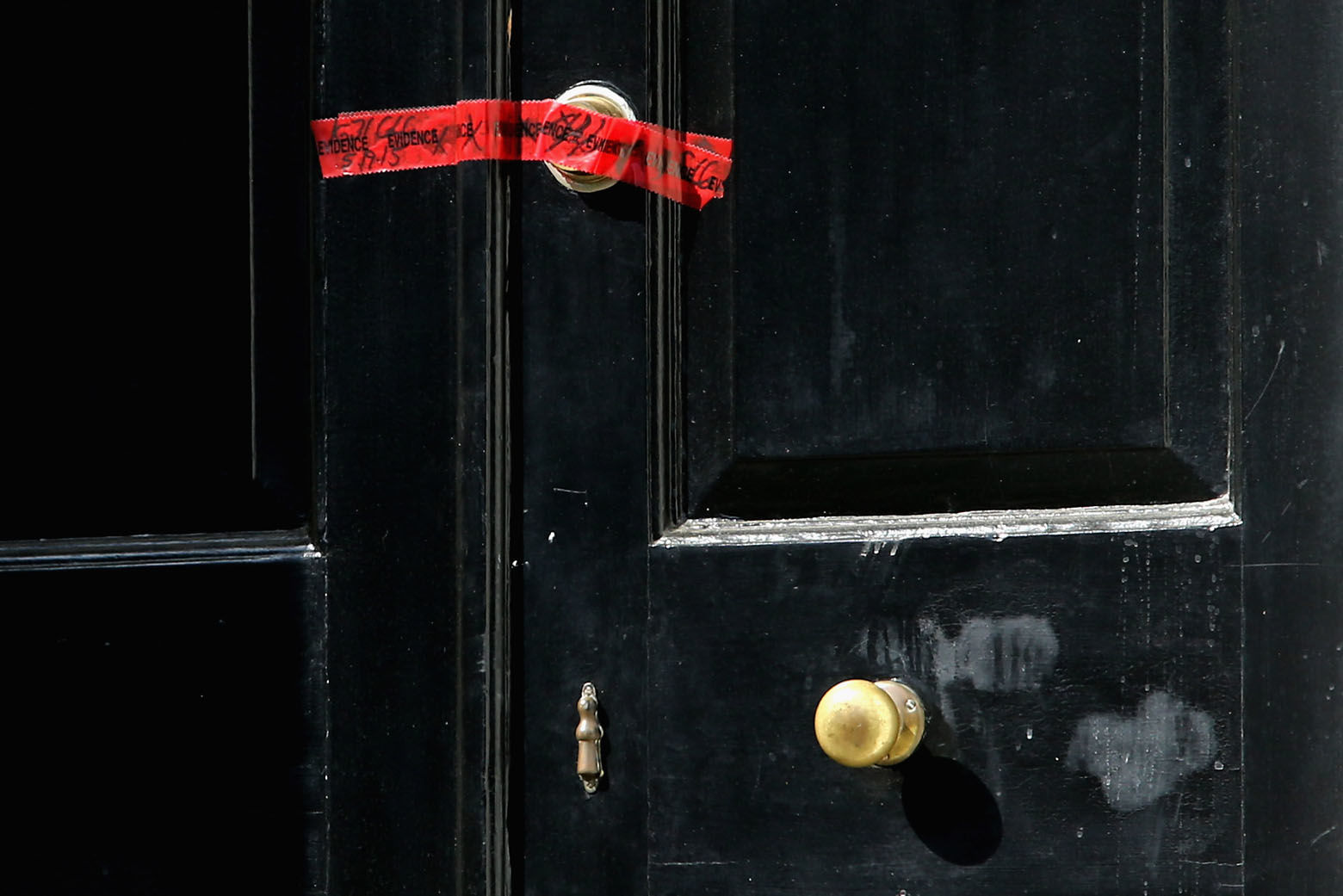 WASHINGTON, DC - MAY 19:  Red crime scene tape seals the front door of a house on the 3200 block of Woodland Drive NW May 19, 2015 in Washington, DC. Firefighters discovered the bodies of Savvas Savopoulos, 46, his wife Amy, 47, their 10-year-old son Philip, and the housekeeper, Veralicia Figueroa, 57, last Thursday afternoon when they responded to a blaze at the house. Two Savopoulos daughters were away in boarding school at the time. Investigators have ruled the deaths homicides and say they could continue to collect evidence at the house for another week.  (Photo by Chip Somodevilla/Getty Images)