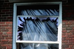 WASHINGTON, DC - MAY 19:  Smashed windows and heavy fire damage scar a house on the 3200 block of Woodland Drive NW May 19, 2015 in Washington, DC. Firefighters discovered the bodies of Savvas Savopoulos, 46, his wife Amy, 47, their 10-year-old son Philip, and the housekeeper, Veralicia Figueroa, 57, last Thursday afternoon when they responded to a blaze at the house. Two Savopoulos daughters were away in boarding school at the time. Investigators have ruled the deaths homicides and say they could continue to collect evidence at the house for another week.  (Photo by Chip Somodevilla/Getty Images)