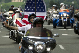 Participants in the Rolling Thunder motorcycle rally waves to the crowds as they ride past Arlington Memorial Bridge, during the annual Rolling Thunder parade, ahead of Memorial Day on Sunday, May 27, 2018, in Washington. (AP Photo/Jose Luis Magana)