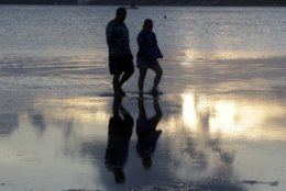 A couple walks along Hobie Beach as the sun sets, Thursday, Aug. 16, 2018, in Miami. (AP Photo/Lynne Sladky)