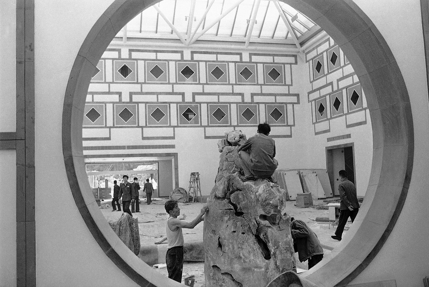 Chinese workers put on the finishing touch on a rockery inside the lobby of Fragrant Hill Hotel in Beijing, China on October 9, 1982, designed by the noted American architect, I.M. Pei, who will preview the hotel next week with visitor Jacqueline Onassis.  (AP Photo/Heung Shing Liu)
