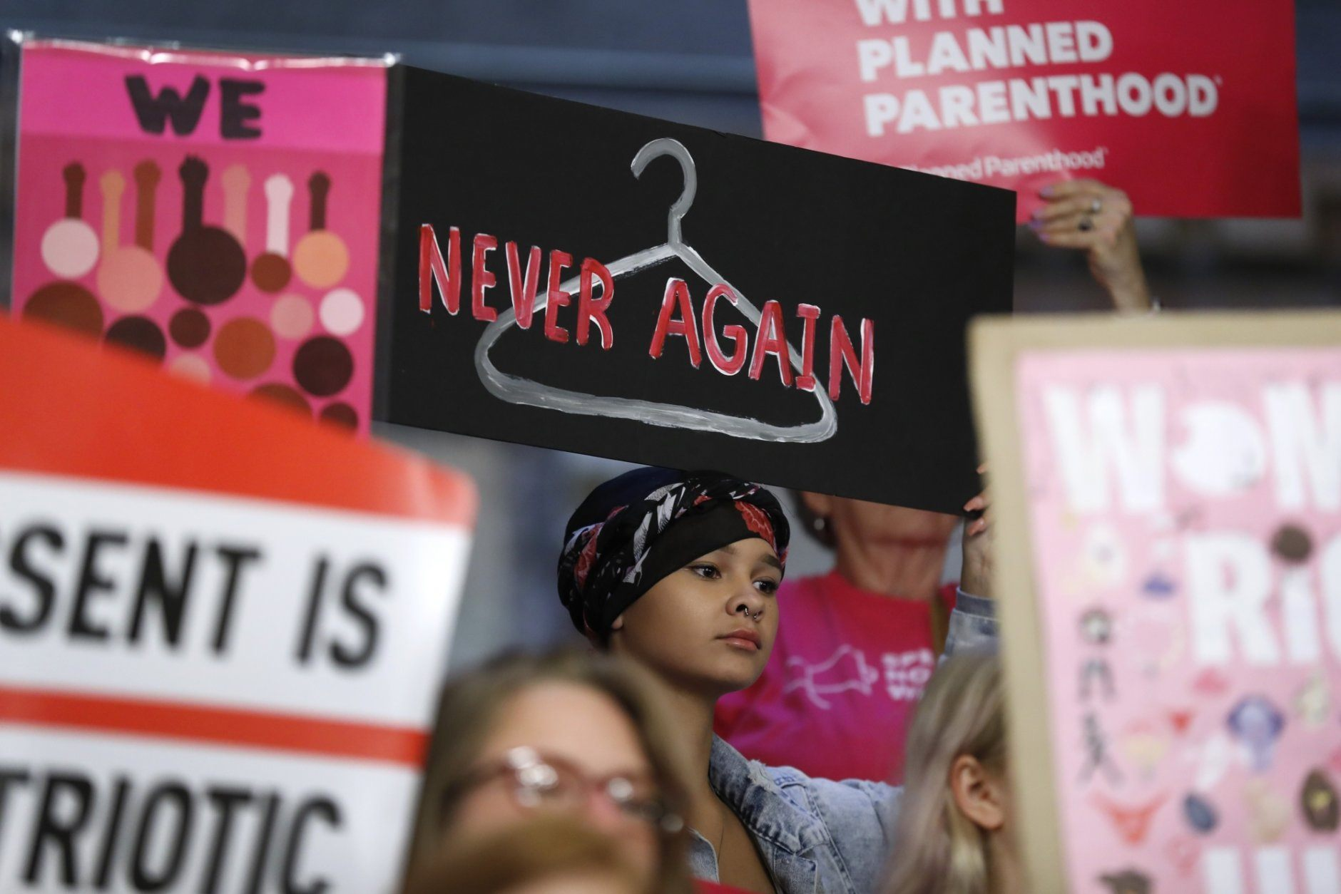 FILE - In this Tuesday, May 21, 2019 file photo, August Mulvihill, of Norwalk, Iowa, center, holds a sign depicting a wire hanger during a rally to protest recent abortion bans put forward in several state legislatures at the Statehouse in Des Moines, Iowa. (AP Photo/Charlie Neibergall)