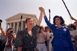 FILE - In this Wednesday, April 26, 1989 file photo, Norma McCorvey, Jane Roe in the 1973 court case, left, and her attorney Gloria Allred hold hands as they leave the Supreme Court building in Washington after sitting in while the court listened to arguments in a Missouri abortion case. A wave of state abortion bans in 2019 has set off speculation: What would happen if Roe v. Wade, the ruling establishing abortion rights nationwide, were overturned? (AP Photo/J. Scott Applewhite, File)