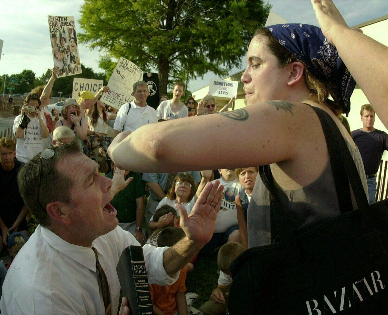 FILE - In this Saturday, July 14, 2001 file photo, abortion-rights activist Karen Nicholls of Chicago, right, shields herself from anti-abortion leader Rev. Flip Benham, left, as Benham attempts to pray for Nicholls during a protest by the two groups , at a Wichita, Kan., abortion clinic. (AP Photo/Charlie Riedel, file)