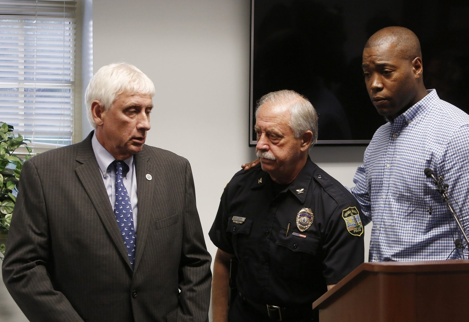 Virginia Beach Mayor Bobby Dyer, left, looks on as City Councilman Aaron Rouse, right, comforts Chief of Police James Cervera following a press conference, Friday, May 31, 2019 in Virginia Beach, Va. A longtime city employee opened fire at a municipal building in Virginia Beach on Friday, killing 11 people before police shot and killed him, authorities said. Six other people were wounded in the shooting, including a police officer whose bulletproof vest saved his life, said Virginia Beach Police Chief James Cervera. (Kaitlin McKeown/The Virginian-Pilot via AP)