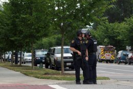 Virginia Beach Police Officers huddle near the intersection of Princess Anne Road and Nimmo Parkway following a shooting at the Virginia Beach Municipal Center on Friday, May 31, 2019 in Virginia Beach, Va, At least one shooter wounded multiple people at a municipal center in Virginia Beach on Friday, according to police, who said a suspect has been taken into custody. (Kaitlin McKeown/The Virginian-Pilot via AP)