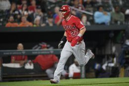Los Angeles Angels' Mike Trout runs toward home to score on a single by Andrelton Simmons during the fifth inning of a baseball game against the Baltimore Orioles on Friday, May 10, 2019, in Baltimore. (AP Photo/Nick Wass)