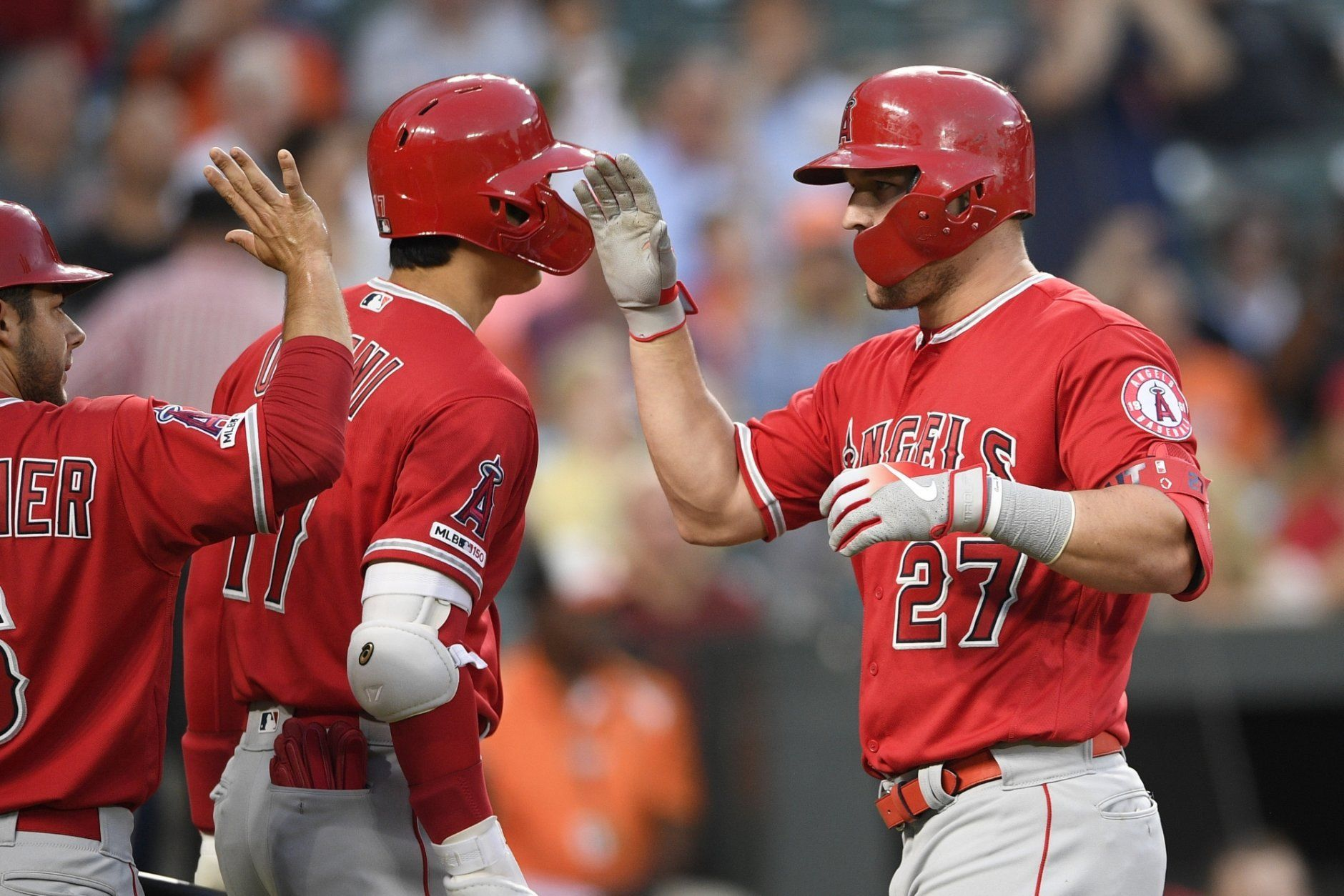 Los Angeles Angels' Mike Trout (27) celebrates his two-run home run with Shohei Ostani, center, of Japan, and David Fletcher, left, during the third inning of the team's baseball game against the Baltimore Orioles, Friday, May 10, 2019, in Baltimore. (AP Photo/Nick Wass)
