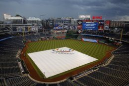 A tarp covers the infield during a rain delay before a baseball game between the St. Louis Cardinals and the Washington Nationals, Thursday, May 2, 2019, in Washington. (AP Photo/Patrick Semansky)