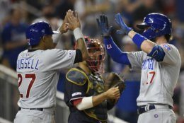 Chicago Cubs' Kris Bryant (17) celebrates his two-run home run with Addison Russell (27) during the seventh inning of a baseball game as Washington Nationals catcher Kurt Suzuki, center, looks on, Friday, May 17, 2019, in Washington. (AP Photo/Nick Wass)
