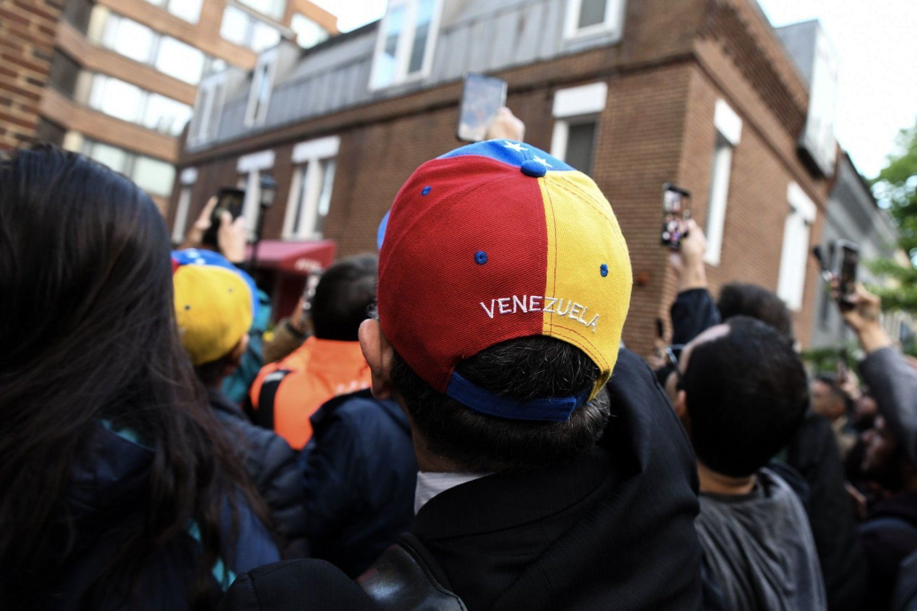 A Venezuelan looks on as a member of Juan Guaido's diplomatic staff speaks with supporters outside the Venezuelan Embassy in Georgetown. (WTOP/Alejandro Alvarez)