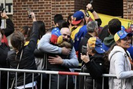 Two Venezuelans embrace in celebration as a months-long occupation of the embassy by pro-Maduro activists seemed to be coming to an end. Arrests had not occurred as of Wednesday morning, though notice had been served that the four activists who remained within were in violation of D.C. and federal law. (WTOP/Alejandro Alvarez)