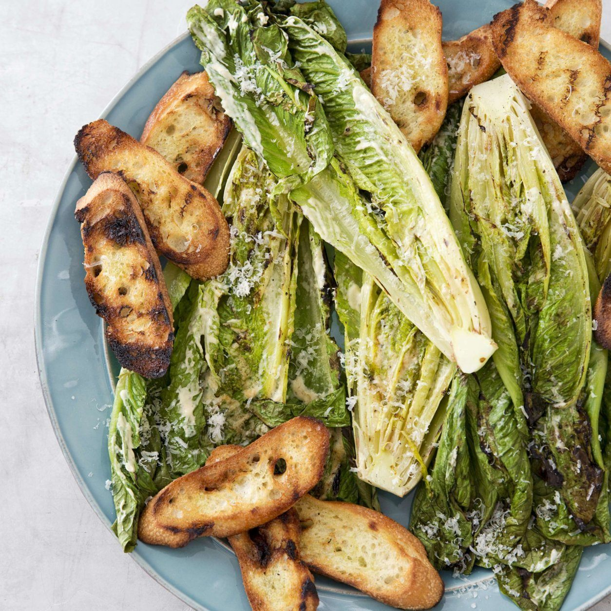 """This undated photo provided by America's Test Kitchen in May 2019 shows Grilled Caesar Salad in Brookline, Mass. This recipe appears in the cookbook """"Vegetables Illustrated."""" (Joe Keller/America's Test Kitchen via AP)"""