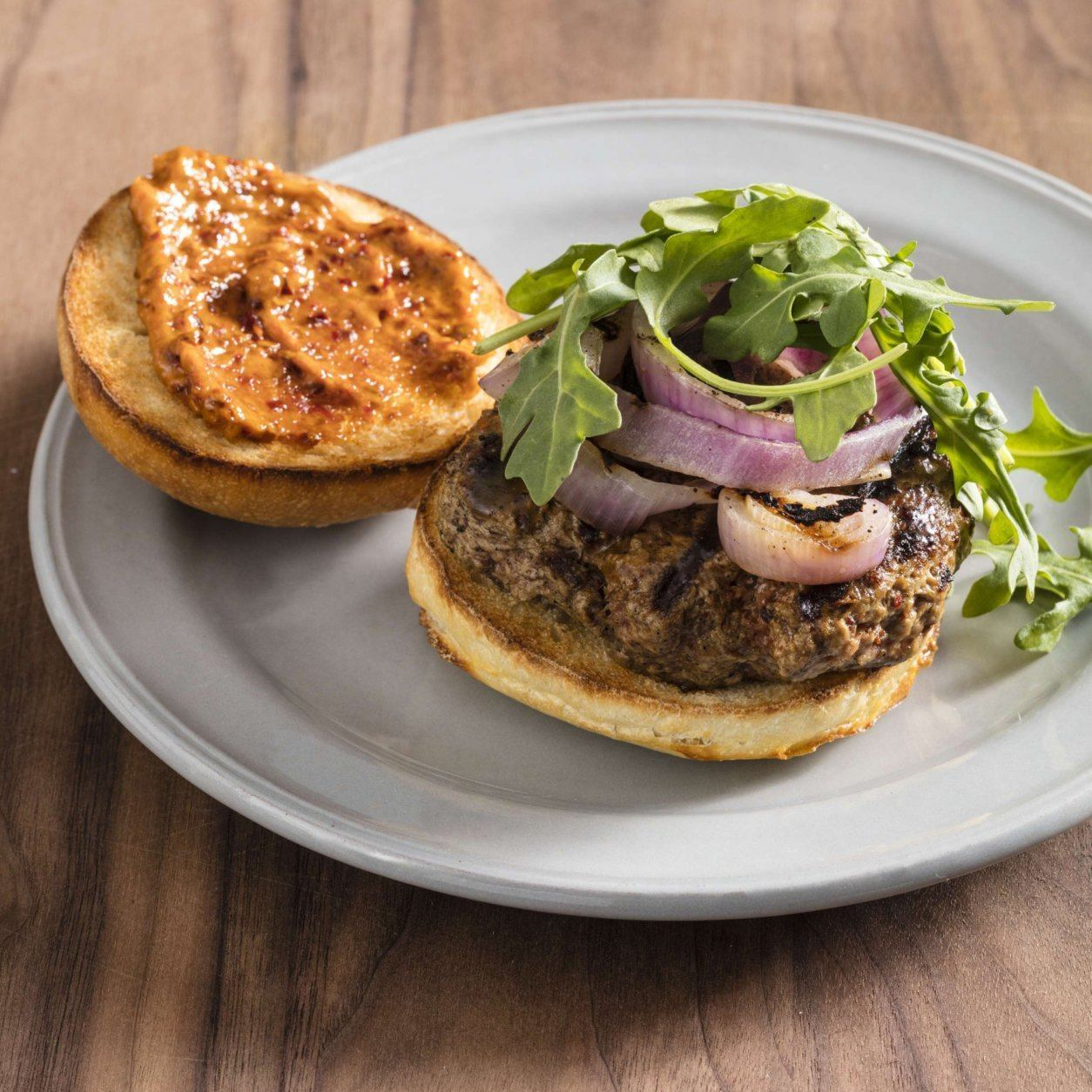 """This undated photo provided by America's Test Kitchen in May 2019 shows Grilled Harissa Lamb Burgers in Brookline, Mass. This recipe appears in the cookbook """"The Ultimate Burger."""" (Daniel J. van Ackere/America's Test Kitchen via AP)"""
