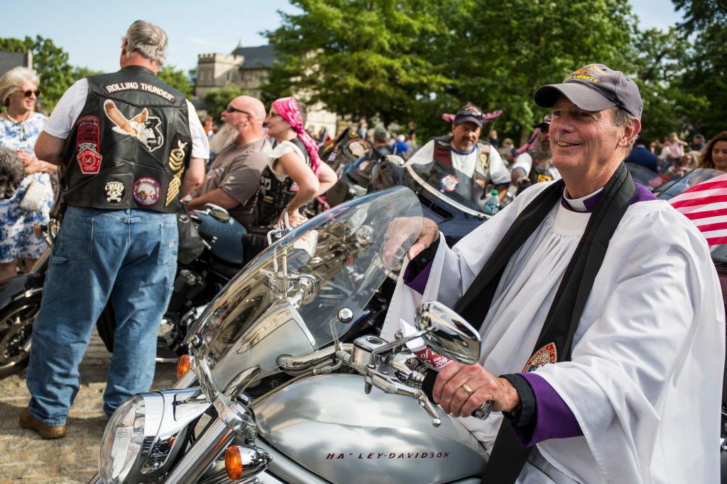 """WASHINGTON, DC - MAY 24: The Rev. Stuart Kenworthy sits on a motorcycle during a blessing of the bikes event at the Washington National Cathedral on May 24, 2019 in Washington, DC. Rolling Thunder will mark the 32nd anniversary of its annual """"Ride for Freedom"""" motorcycle procession and commemorative events this Memorial Day weekend for raising the attention of POW and MIA issues (Photo by Zach Gibson/Getty Images)"""