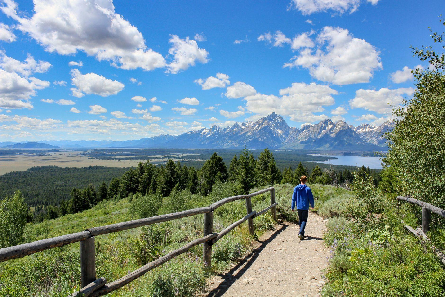 Teenage boy hiking with Jackson lake and mount Teton view in summer