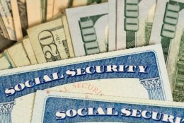 USA Social security cards laid on pile of dollar bills to illustrate money in retirement