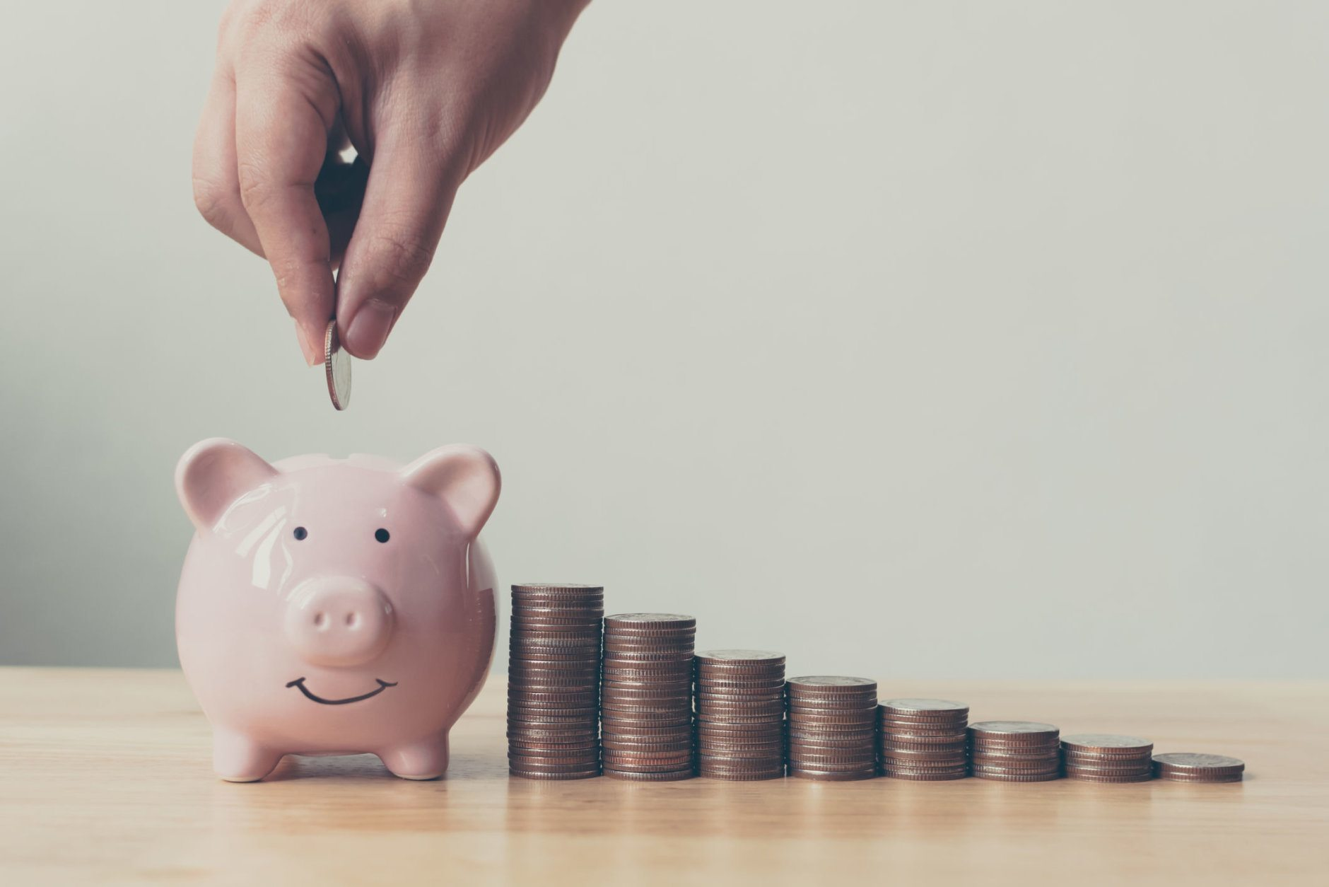 Hand of male or female putting coins in piggy bank with money stack step growing growth saving money. Concept finance business investment