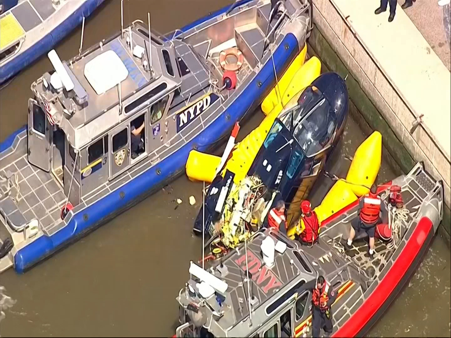 In this image made from video provided by WABC-TV, harbor units from the New York City police and fire departments work to secure a helicopter to the dock after it crashed in the Hudson River, Wednesday, May 15, 2019 in New York. WABC reports that the pilot was ok and that there were no passengers on the aircraft. (WABC-TV via AP)