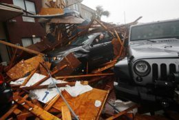 FILE - In this Oct. 10, 2018, file photo, a storm chaser climbs into his vehicle to retrieve equipment after a hotel canopy collapsed, as the eye of Hurricane Michael passes over Panama City Beach, Fla. For some communities, the devastation remains an open wound, as in Florida's Panama City, slammed by Hurricane Michael last year. (AP Photo/Gerald Herbert, File)