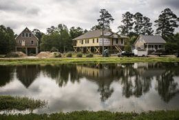 In this May 13, 2019, photo new homes are built on pillars along the Little Pee Dee River, in Nichols, S.C. Nichols suffered devastating flooding during Hurricane Matthew 2016 and Florence in 2018. (AP Photo/Sean Rayford)