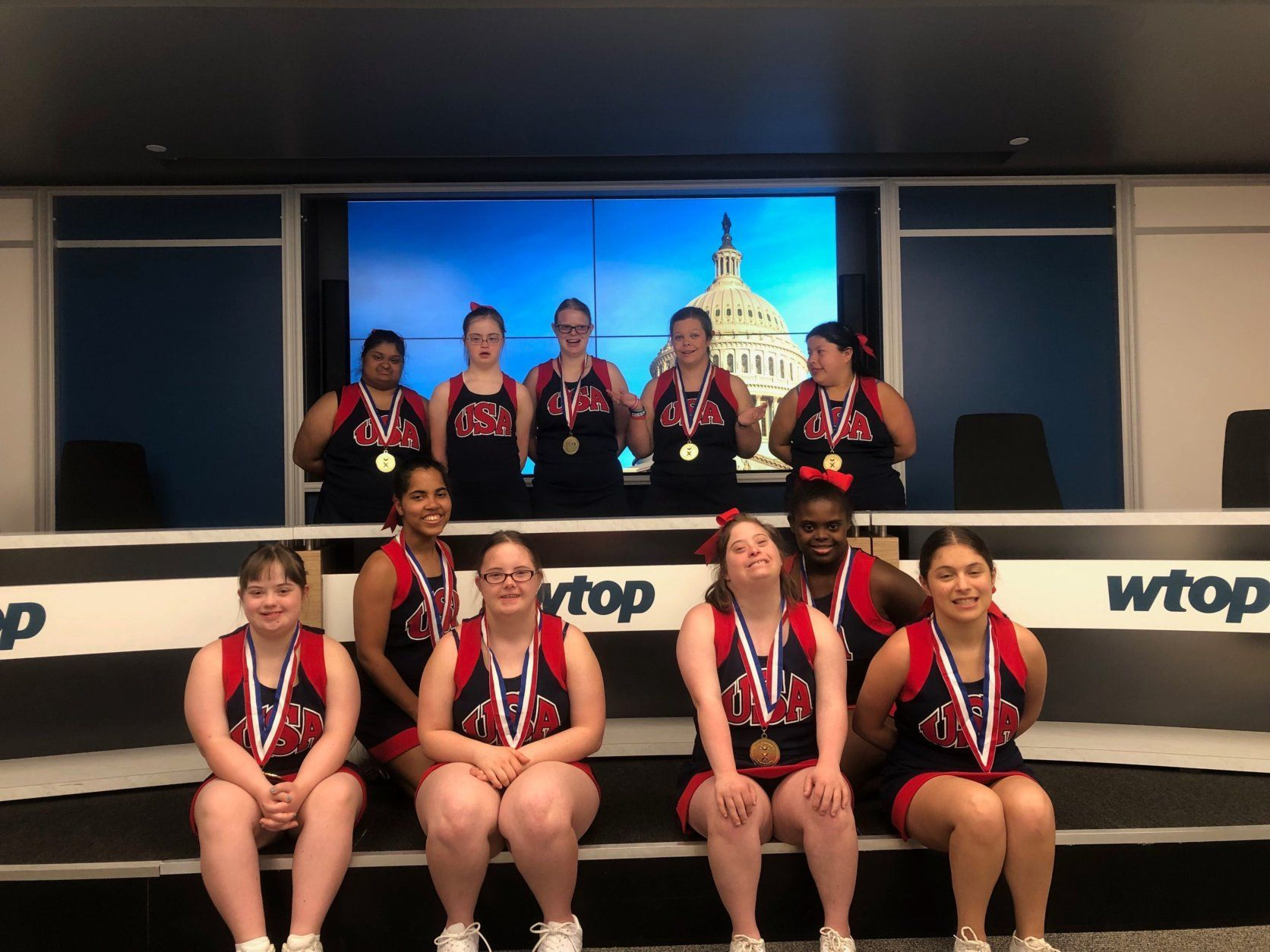 The JOY Supernovas, pictured here visiting the WTOP studios, became the first Special Olympics traditional cheerleading team to compete and win at the Cheerleading World Championships. (WTOP/Mike Murillo)