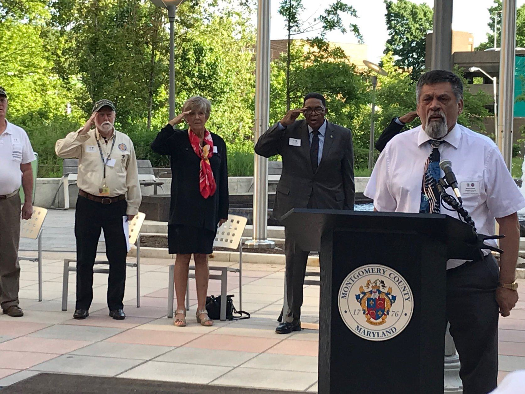 Vietnam veteran Wayne Miller sings the national anthem at a ceremony marking the anniversary since the dedication of the Montgomery County Vietnam Veterans Memorial wall in Rockville, Maryland. (WTOP/Michelle Basch)