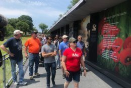 Visitors walk along the Poppy Wall of Honor. (WTOP/Dick Uliano)