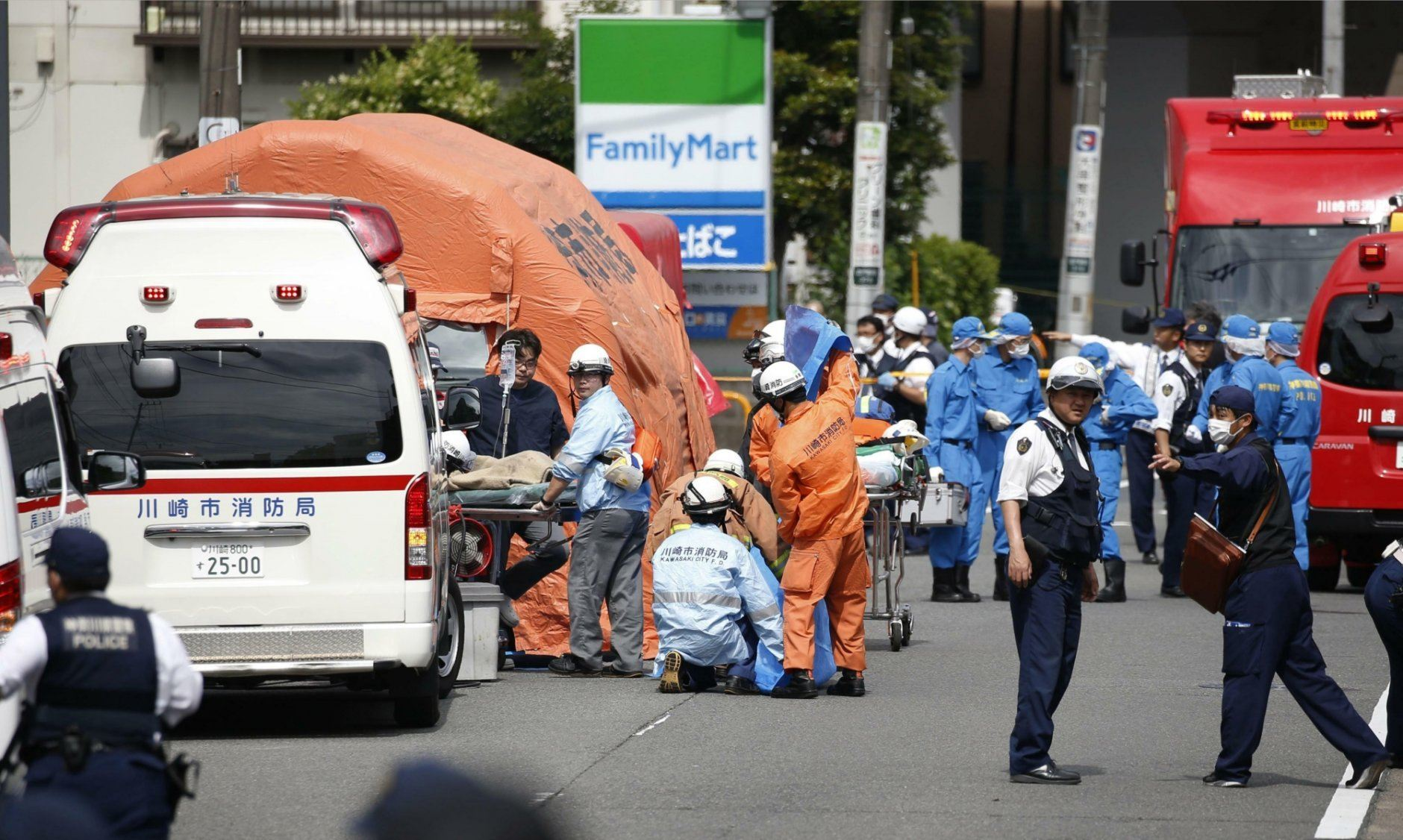 Rescuers work at the scene of an attack in Kawasaki, near Tokyo Tuesday, May 28, 2019. A man wielding a knife attacked commuters waiting at a bus stop just outside Tokyo during Tuesday morning's rush hour,  Japanese authorities and media said. (Kyodo News via AP)