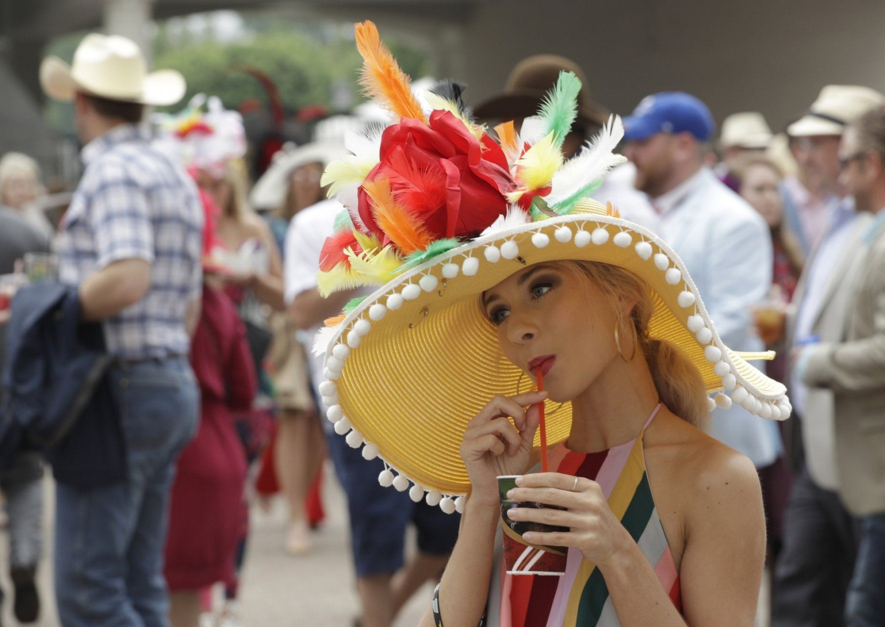 In this photo taken with long time exposure, a woman wears a hat at Churchill Downs before the 145th running of the Kentucky Derby horse race Saturday, May 4, 2019, in Louisville, Ky. (AP Photo/Charlie Riedel)