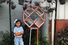 Lana Basri standing next to her Free Little Library in West Java, Indonesia. (Courtesy Basri family)